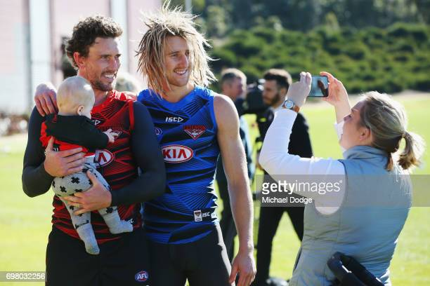 Heath Hocking and Dyson Heppell of the Bombers of the Bombers pose with a fans baby during an Essendon Bombers AFL training session at True Value...