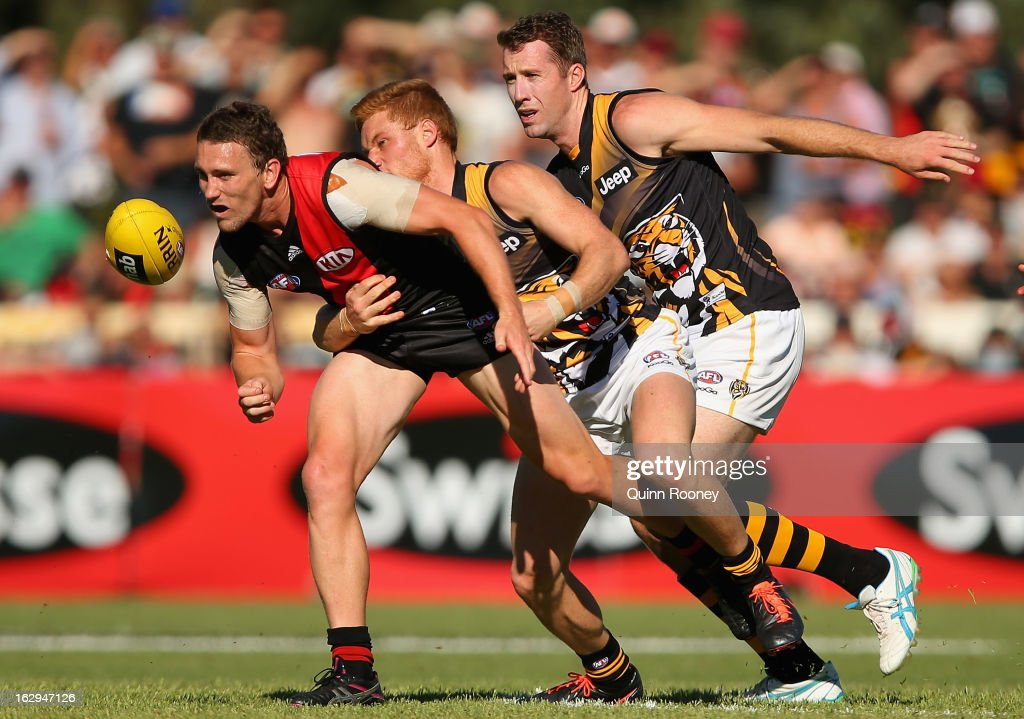 Heath Hocking of the Bombers handballs whilst being tackled by Nick Vlastuin of the Tigers during the round two AFL NAB Cup match between the Essendon Bombers and the Richmond Tigers at Wangaratta Showgrounds on March 2, 2013 in Wangaratta, Australia.