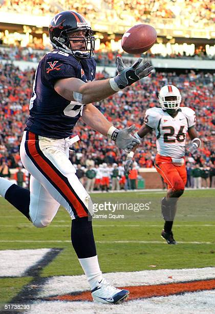 Heath Miller of the Virginia Cavaliers catches a pass for a touchdown as Anthony Reddick of the Miami Hurricanes looks on during the first half of...