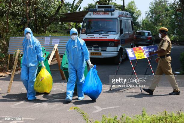 Heath officials in full protective apparel carry medical waste out of an isolation ward of Ernakulam medical, where 12 suspected SARS-like virus...