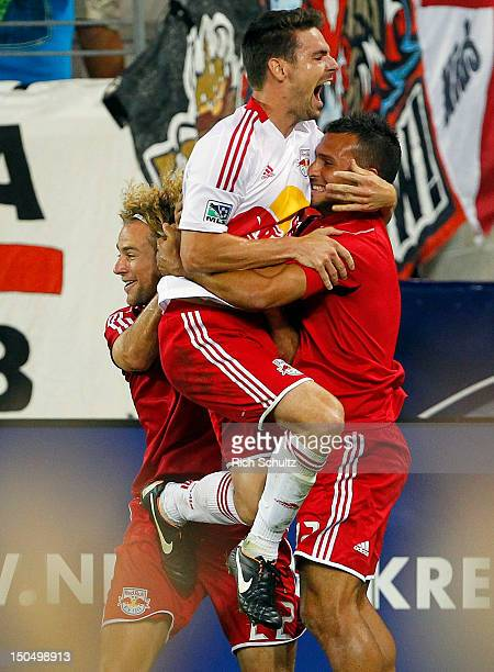 Heath Pearce of the New York Red Bulls celebrates his game winning goal by jumping in the arms of teammate Jonathan Borrajo as Stephen Keel grabs...