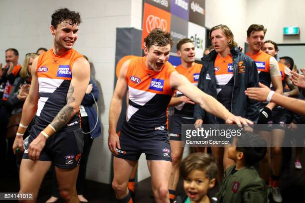 Heath Shaw of the Giants and team mates celebrate as they greet fans in their changeroom after winning the round 19 AFL match between the Greater...