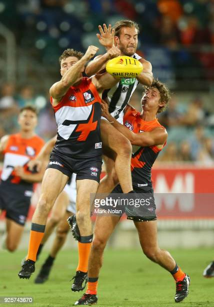 Heath Shaw of the Giants and Tim Broomhead of the Magpies contest possession during the JLT Community Series AFL match between the Greater Western...