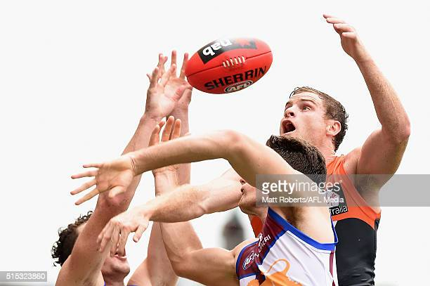 Heath Shaw of the Giants competes for the ball against Jonathan Freeman and Daniel McStay of the Lion during the NAB Challenge AFL match between the...