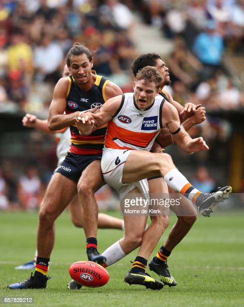 Heath Shaw of the Giants is tackled by Troy Menzel and Charlie Cameron of the Crows during the round one AFL match between the Adelaide Crows and the...