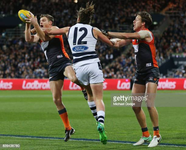 Heath Shaw of the Giants marks the ball against Wylie Buzza of the Cats during the round 23 AFL match between the Geelong Cats and the Greater...