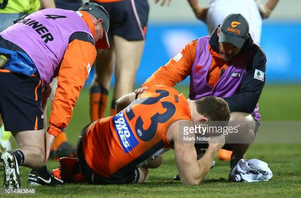 Heath Shaw of the Giants receives attention for an injury from the field during the round 21 AFL match between the Greater Western Giants and the...