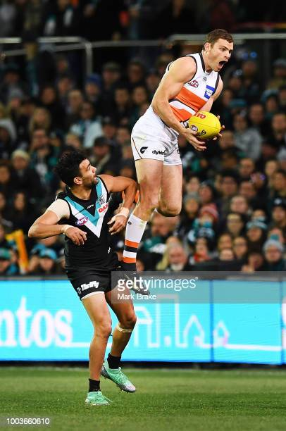 Heath Shaw of the Giants takes a huge leaping mark over Lindsay Thomas of Port Adelaide during the round 18 AFL match between the Port Adelaide Power...