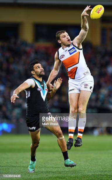 Heath Shaw of the Giants taps the ball in front of Lindsay Thomas of Port Adelaide during the round 18 AFL match between the Port Adelaide Power and...