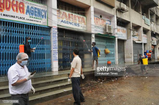 Heath workers chemically sanitize shops at Gobind Mitra road on June 30 2020 in Patna India