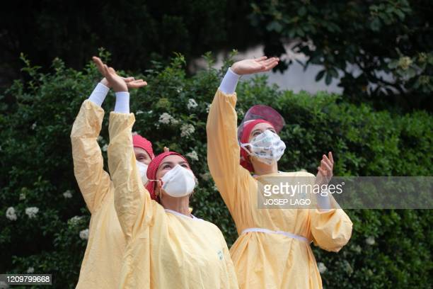 Heathcare workers wearing face masks and protective suits acknowledge applause outside the Hospital de Barcelona on April 13 2020 in Barcelona during...