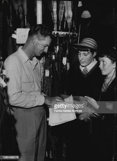 Heather and Janice Howard of Beverley Hills identify their umbrella to Mr Roger Hankison at the Railway Lost Property Office today March 21 1956