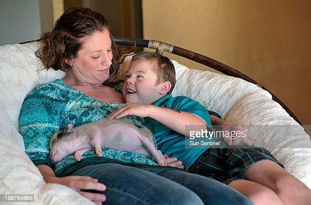 Heather and Kason Ray relax with Twinkie, their new Juliana Pig, Thursday, November 8, 2012 in Coral Gables, Florida. The fight over a pig named...