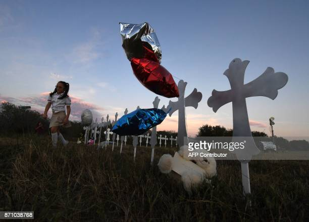 TOPSHOT Heather Cooper leaves after placing her favorite doll on a row of crosses for each victim after a mass shooting that killed 26 people in...