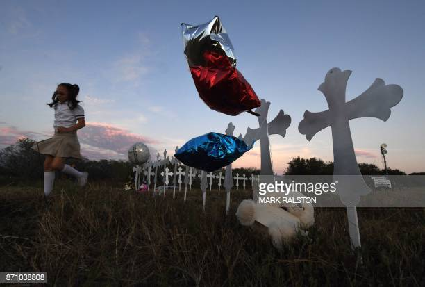 Heather Cooper leaves after placing her favorite doll on a row of crosses for each victim after a mass shooting that killed 26 people in Sutherland...
