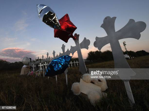 Heather Cooper places her favorite doll on a row of crosses for each victim after a mass shooting that killed 26 people in Sutherland Springs Texas...
