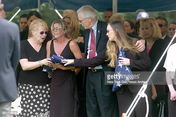 Heather Duggan is comforted by her mother and Daniel and Maureen Murphy during funeral services for the Murphy's son Michael Murphy at Calverton...