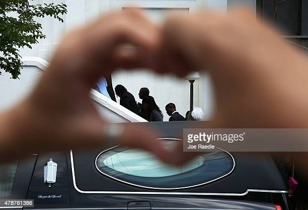 Heather Hayward forms a heart with her hands as mourners file in for the funeral of Cynthia Hurd at the Emanuel African Methodist Episcopal Church...