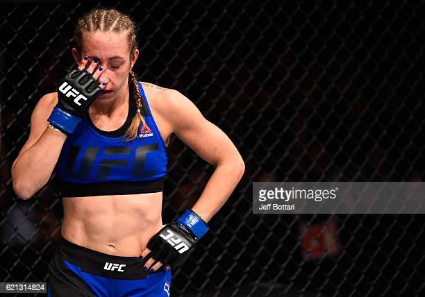 Heather Jo Clark of the United States rubs her eye after the first round while facing Alexa Grasso of Mexico up against the cage in their women's...