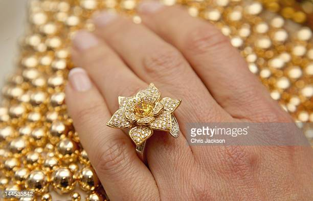 Heather Kerzner poses wearing the George Pragnell Daffodil Ring set with a rare oval fancy vivid orange/yellow diamond donated by jeweller George...