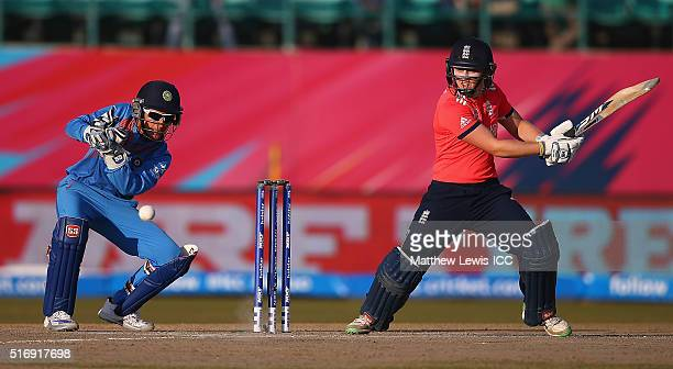 Heather Knight of England hits the bal towards the boundary as Sushma Verma of India looks on during the Women's ICC World Twenty20 India 2016 match...