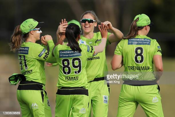 Heather Knight of the Thunder celebrates with team mates after taking the wicket of Heather Graham of the Scorchers during the Women's Big Bash...