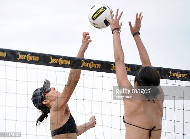 Heather Lowe tips the ball over the hands of Mariko Coverdale in their match during the Manhattan Beach Open at Manhattan Beach on August 26 2011 in...