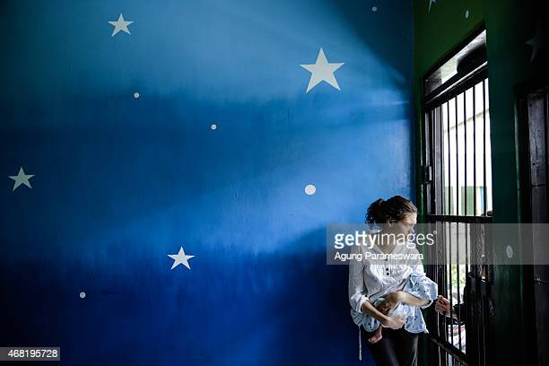 Heather Mack of the US holds her baby in a cell while she talk with his relative before her sentence demand trial on March 31, 2015 in Denpasar,...