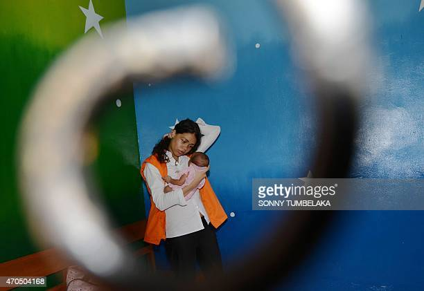 Heather Mack of the US holds her baby inside a holding cell before her trial hearing at a court in Denpasar on the resort island of Bali on April 21,...