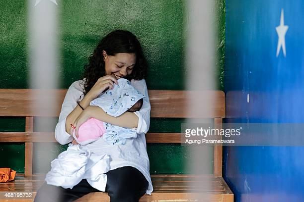 Heather Mack of the US smiles as she hold her baby in a cell before her sentence demand trial on March 31, 2015 in Denpasar, Bali, Indonesia....