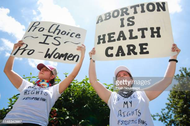 Heather Masson left and Victoria Jernigan hold signs promoting a woman's right to choose during a protest against recently passed abortion ban bills...