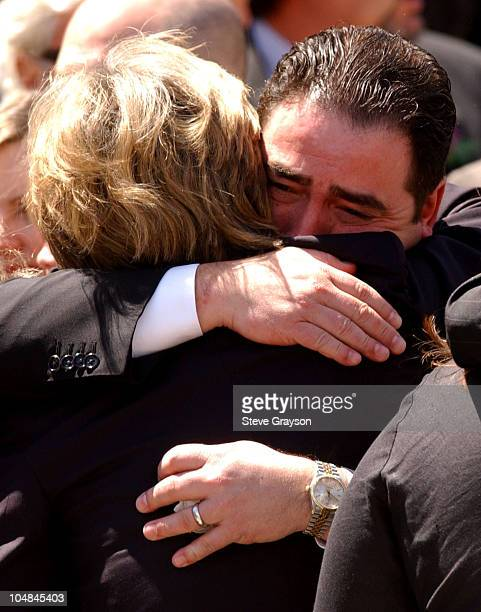 Heather Menzies widow of actor Robert Urich is comforted by Emeril Lagasse after funeral services for the actor April 19 2002
