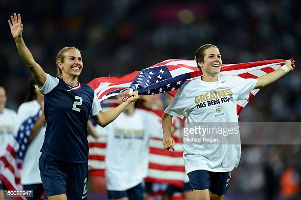 Heather Mitts and Kelley O'Hara of the United States celebrate with the Amrican flag after defeating Japan by a score of 21 to win the Women's...