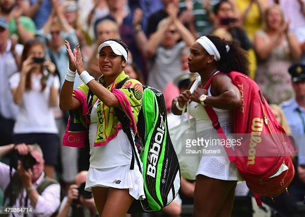 Heather Watson of Great Britain applauds the fans on Centre Court after defeat as her and Serena Williams of the United States leave the court after...