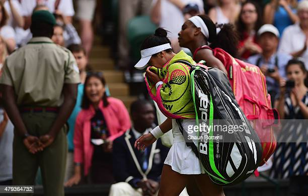 Heather Watson of Great Britain wipes her face with a towel after defeat as her and Serena Williams of the United States leave the court after their...