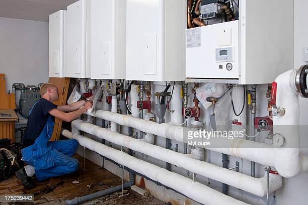 Heating and sanitary technician testing and adjusting a gas heater