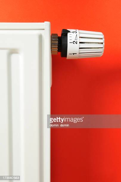 Heating, close-up of thermostat and radiator on red background