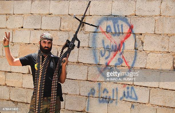 A heavily armed Iraqi Shiite fighter from the Popular Mobilisation units flashes the V for victory sign in front of graffiti of the Islamic State...