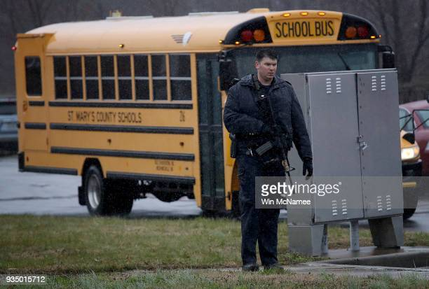 A heavily armed law enforcement officer stands guard as students from Great Mills High School are evacuated to Leonardtown High School following a...