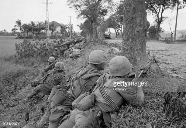Heavily armed Marines lie prone on a roadside ridge providing cover for buddies who approach a solitary house in search of Viet Cong during a search...