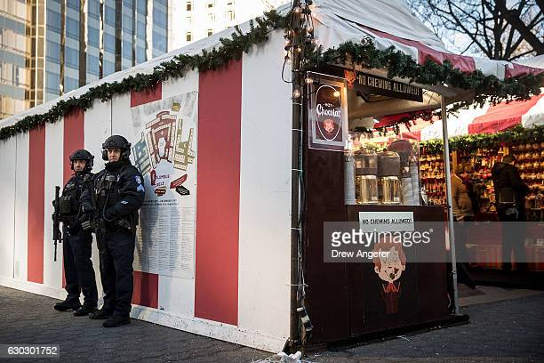 Heavily armed New York City Police officers stand guard at the Columbus Circle Holiday Market December 20 2016 in New York City Following the fatal...