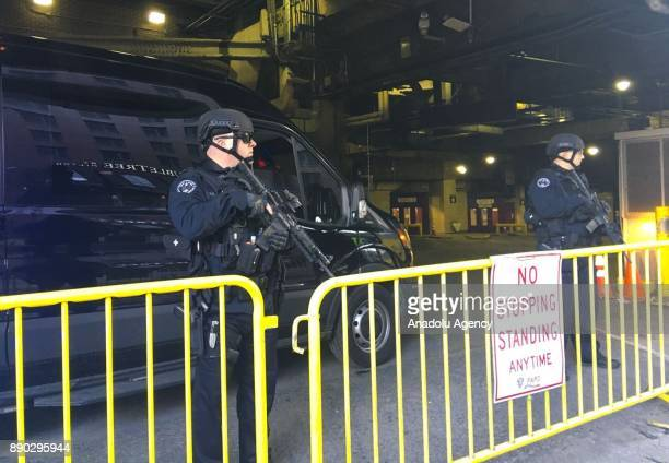 Heavily armed New York Police Department officers stand behind a road blocking with a plate reading' No Stopping Standing Anytime PAPD after an...