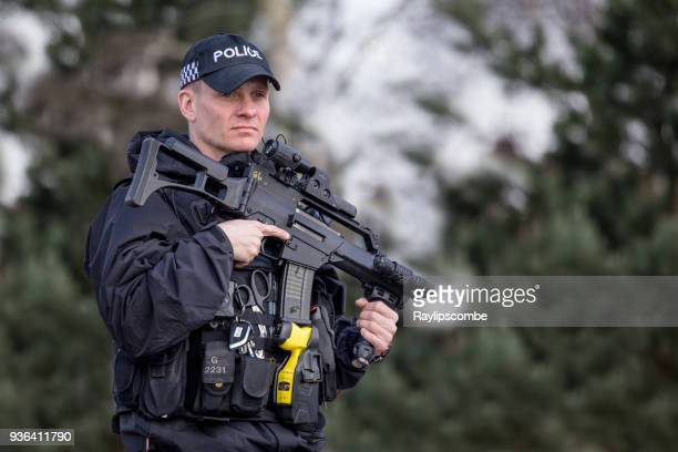 heavily armed police officer, against a blurred foliage background, with no people and embedded clipping path - police taser stock pictures, royalty-free photos & images