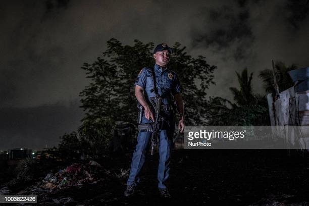 A heavily armed police officer secures the scene where two suspected drug dealers were killed by police during a drug sting operation in Manila...