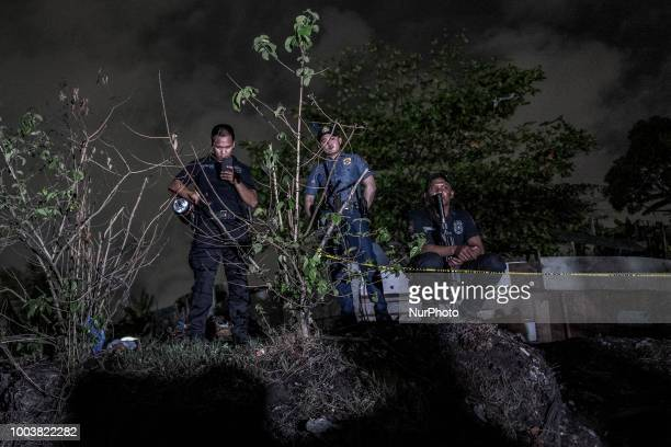 Heavily armed police officers secure the scene where two suspected drug dealers were killed by police during a drug sting operation in Manila...
