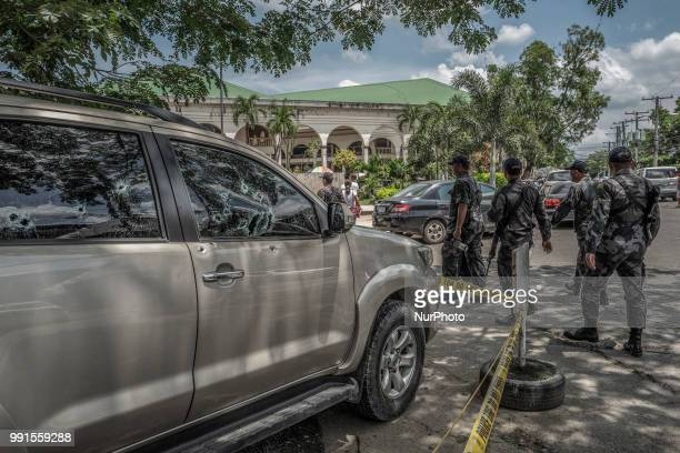Heavily armed police officers walk past the bullet riddled vehicle of General Tinio Mayor Ferdinand Bote who was assassinated by unidentified gunmen...
