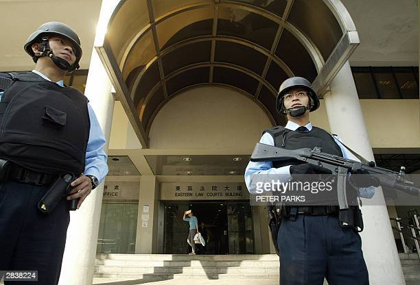 Heavily armed police stand guard outside Eastern Court as Hong Kong's most wanted man Kwai Pinghung appears for a hearing 31 December 2003 Kwai is...