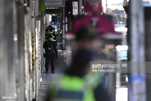 A heavily armed policeman stands guard as emergency personnel work at the scene of where a car ran over pedestrians in Flinders Street in Melbourne...