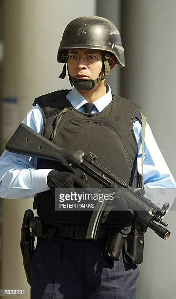 A heavily armed policeman stands guard outside Eastern Court as Hong Kong's most wanted man Kwai Pinghung appears for a hearing 31 December 2003 Kwai...