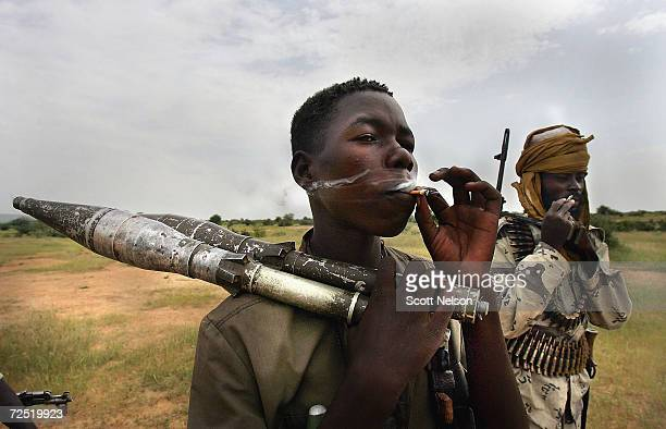 Heavily armed rebel fighters from the Sudanese Justice and Equality Movement smoke one of their rationed cigarettes at their base in the Darfur...